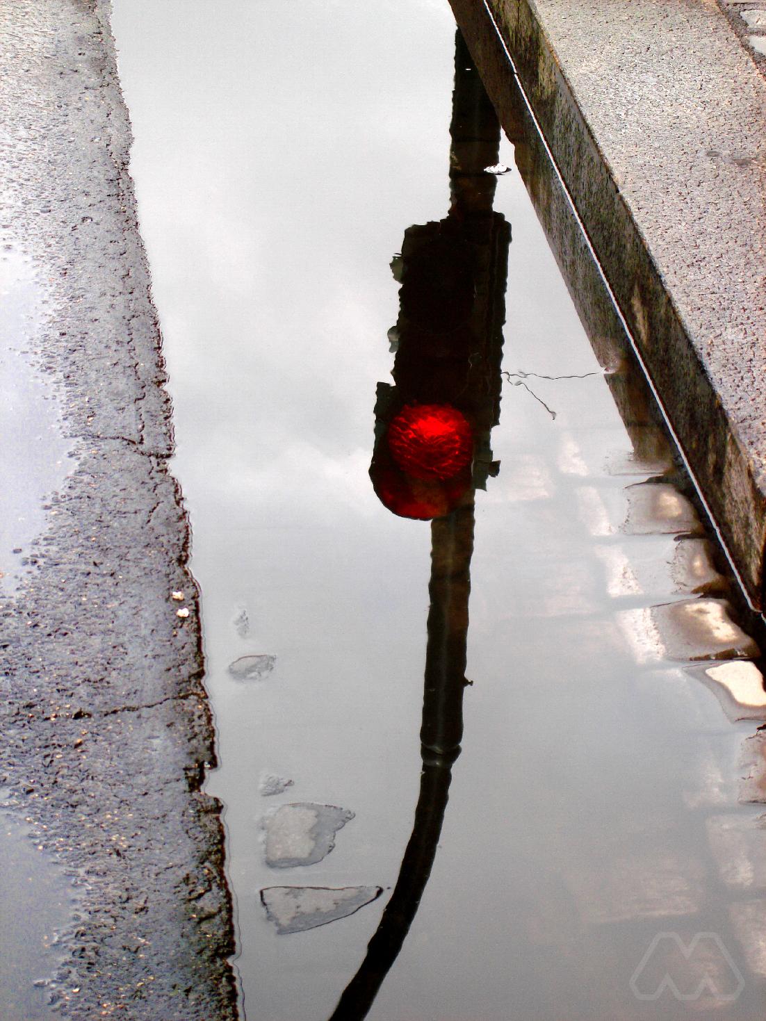 Semaforo in rosso riflesso su pozzanghera a Roma