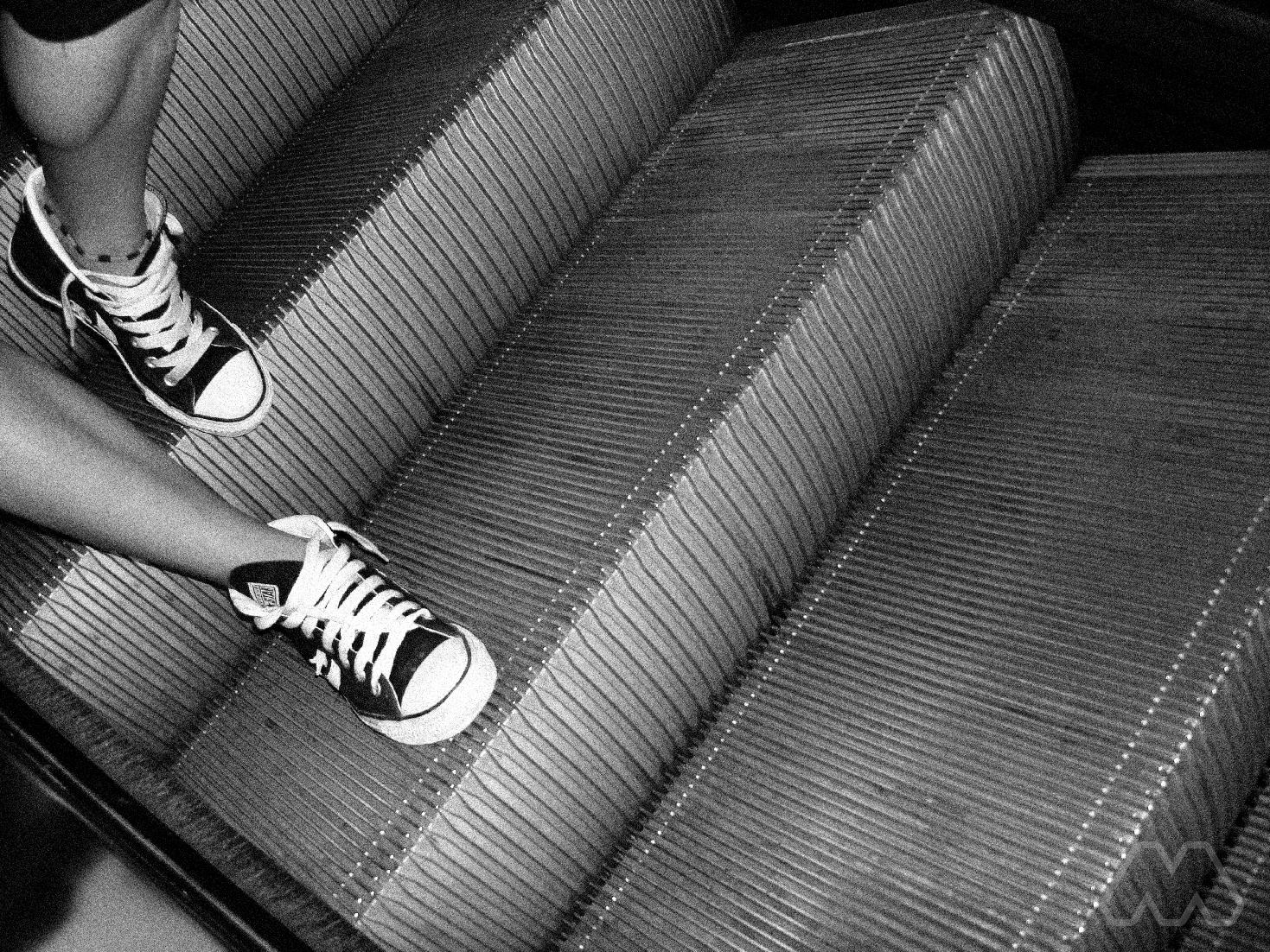 Chica bajando escaleras mecánicas